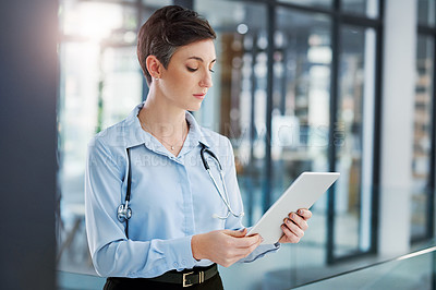 Buy stock photo Cropped shot of an attractive young female doctor using her tablet while standing in the hospital