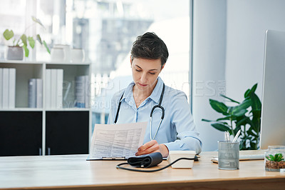 Buy stock photo Cropped shot of an attractive young female doctor looking over paperwork while sitting at her desk in the office
