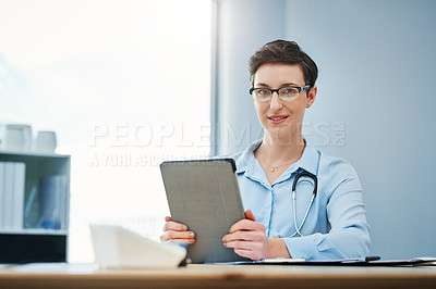 Buy stock photo Cropped portrait of an attractive young female doctor using her tablet while sitting at her desk in the hospital
