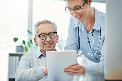 Buy stock photo Cropped shot of two doctors looking over a tablet in their office together