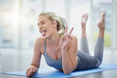 Buy stock photo Shot of a sporty young woman making a funny face while exercising in a studio
