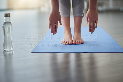 Buy stock photo Closeup shot of an unrecognizable woman bending down to touch her feet while exercising in a studio