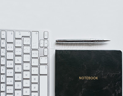 Buy stock photo Shot of a computer keyboard and notebook on a work desk in a modern office