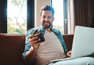 Buy stock photo Cropped shot of a handsome young man shopping online while chilling on the sofa at home