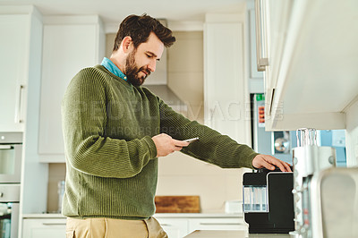 Buy stock photo Cropped shot of a handsome young man using his cellphone in the kitchen at home