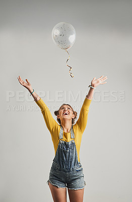 Buy stock photo Studio shot of an attractive young woman playing with a balloon against a grey background