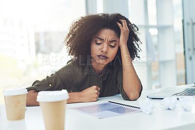 Buy stock photo Shot of a young businesswoman sitting at her office desk looking stressed out and a bit confused