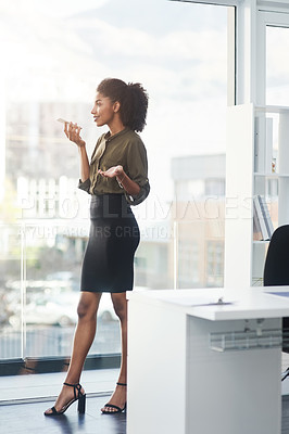 Buy stock photo Full length shot of a young businesswoman standing in her office and busy talking on a smartphone