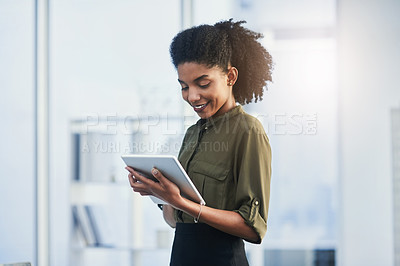 Buy stock photo Shot of a young businesswoman using her digital tablet in a office