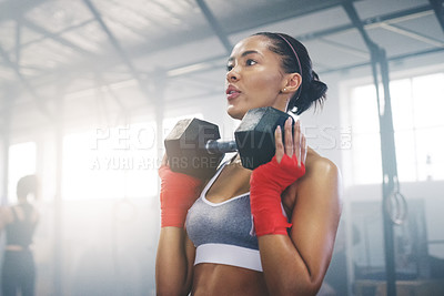 Buy stock photo Cropped shot of a focused young sportswoman busy working out in the gym