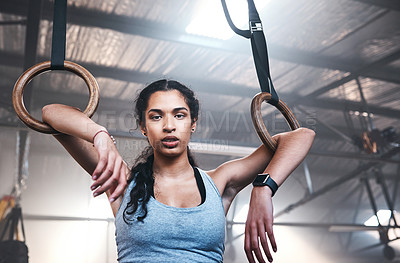 Buy stock photo Cropped portrait of an attractive and athletic young woman working out on the gymnastic rings in the gym