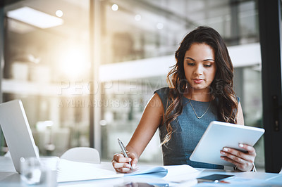 Buy stock photo Cropped shot of an attractive young businesswoman writing notes while working on her tablet in the office