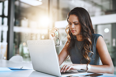 Buy stock photo Cropped shot of an attractive young businesswoman looking stressed while working on her laptop in the office