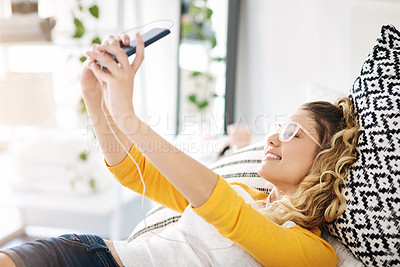 Buy stock photo Cropped shot of an attractive young woman listening to music and taking selfies while lying on her bed at home