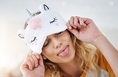 Buy stock photo Cropped shot of an attractive young woman wearing a sleeping mask and sticking her tongue out while relaxing in her bedroom at home