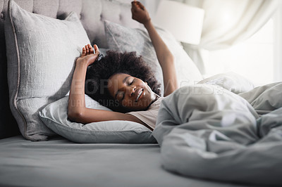 Buy stock photo Shot of a happy young woman waking up in her bed at home