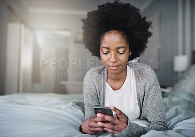 Buy stock photo Shot of a young woman using a mobile phone in her bed at home