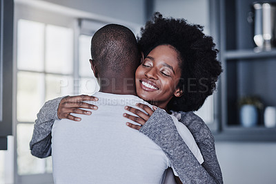 Buy stock photo Shot of a happy young couple embracing at home