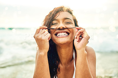 Buy stock photo Cropped portrait of an attractive young woman making a moustache out of her hair while standing on the beach