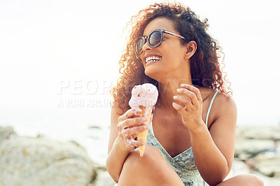 Buy stock photo Cropped shot of an attractive young woman eating a melting ice cream while sitting on the beach