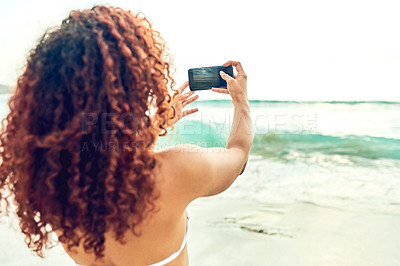 Buy stock photo Rearview shot of an unrecognizable young woman taking photographs while standing on the beach