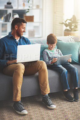 Buy stock photo Shot of a cheerful little boy and his father using a laptop and a digital tablet while being seated on a sofa at home during the day