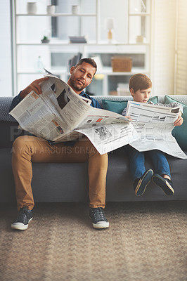 Buy stock photo Shot of a carefree little boy and his father reading the newspaper while being seated on the sofa at home during the day