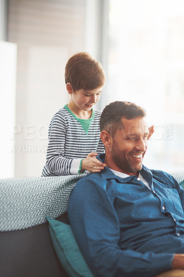 Buy stock photo Shot of a carefree little boy giving his father a massage on his shoulders while he relaxes on the sofa at home