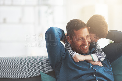 Buy stock photo Shot of a cheerful little boy giving his father a hug from behind while his father relaxes on the sofa at home