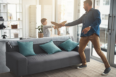 Buy stock photo Shot of a cheerful little boy and his father playing around together while being in the living room