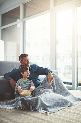 Buy stock photo Shot of a carefree young boy and his father watching a movie together while being seated on the floor at home during the day