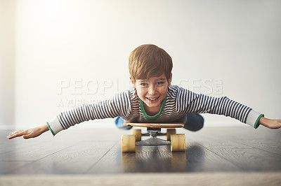 Buy stock photo Portrait of a cheerful little boy lying down on a skateboard at home during the day