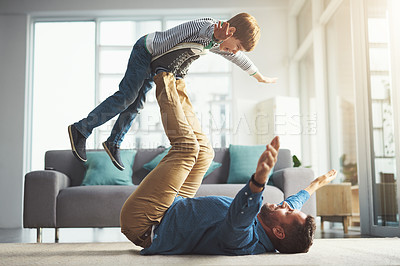 Buy stock photo Shot of a cheerful little boy playing around and being lifted by his dad with his legs in the living room at home during the day