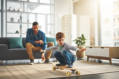 Buy stock photo Shot of a cheerful little boy riding on a surfboard in the middle of the living room at home