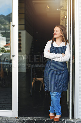 Buy stock photo Portrait of a confident young woman standing in the doorway of a coffee shop
