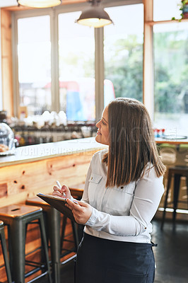 Buy stock photo Shot of a young entrepreneur making notes in her cafe