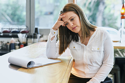 Buy stock photo Shot of a young entrepreneur looking stressed while doing paperwork in her cafe