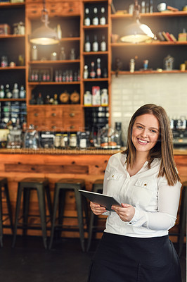 Buy stock photo Shot of a young entrepreneur using a digital tablet in her cafe