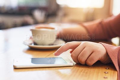 Buy stock photo Shot of an unrecognizable woman using her cellphone while sitting in a coffee shop