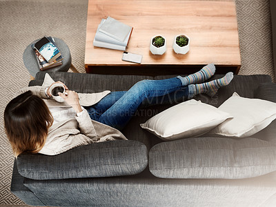 Buy stock photo Shot of an attractive young woman sitting on her sofa while  relaxing at home drinking coffee