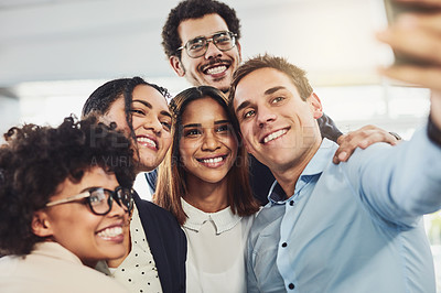 Buy stock photo Shot of a group of cheerful work colleagues taking a self portrait together inside of the office during the day
