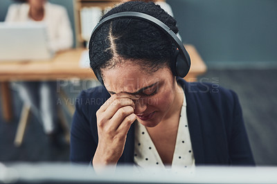 Buy stock photo Shot of a stressed out young businesswoman working on her computer while listening to a client over the phone inside the office at work