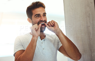 Buy stock photo Cropped shot of a handsome young man flossing his teeth while looking at his reflection in the mirror at home