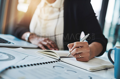 Buy stock photo Cropped shot of a businesswoman making notes at her desk in a modern office