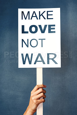 "Buy stock photo Studio shot of an woman holding a sign that says ""make love not war"" against a blue background"