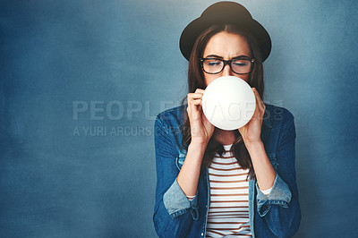 Buy stock photo Studio shot of an attractive young woman blowing up a balloon against a blue background
