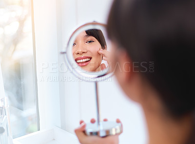 Buy stock photo Shot of a cheerful attractive young woman applying moisturizer on her face while looking into her reflexion in the mirror