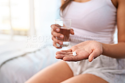 Buy stock photo Shot of an unrecognizable young woman taking medication with a drink of water at home  in the morning