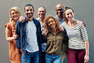 Buy stock photo Portrait of a group of people standing together against a wall outside