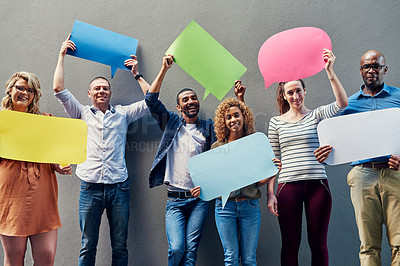Buy stock photo Portrait of a group of people holding speech bubbles against a wall outside
